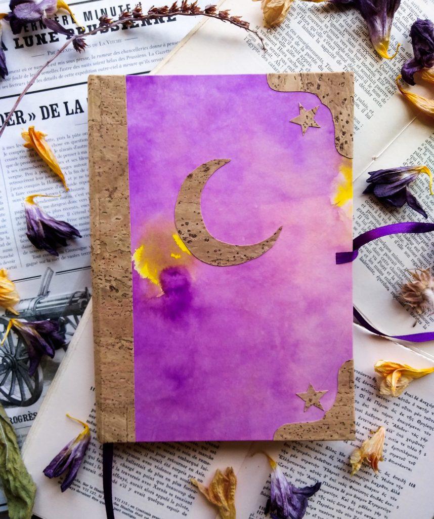 Photographie d'un carnet en liège avec une lune en liège sur fond papier coloré à l'encre violette