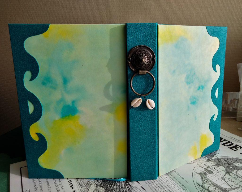 Photographie du grimoire océan, où l'on voit l'ensemble de sa couverture, avec un dos en simili cuir bleu avec une décoration cuivre et coquillage, et un papier de couverture à l'encre bleue et jaune.