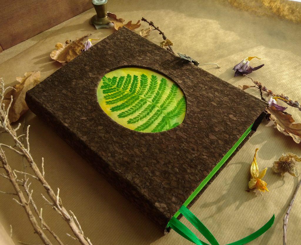 Photographie du grimoire du botaniste, en liège avec une peinture de fougère encadrée sur le devant de la couverture.