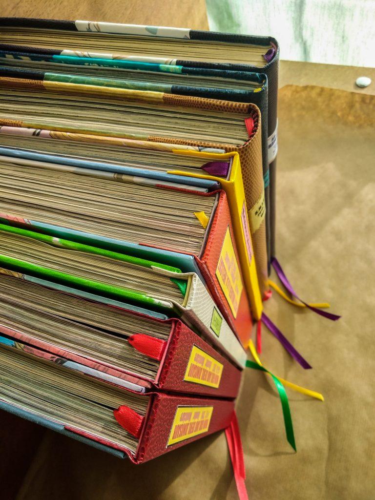 Photographie vue de haut de plusieurs reliures de comics, où l'on voit des dos carrés et ronds, et les signets colorés