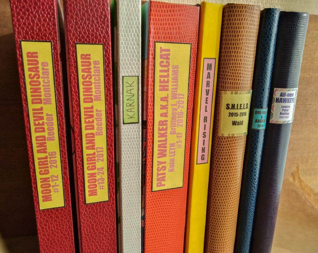Photographie de plusieurs dos de comics reliés, où l'on voit des dos ronds et carrés, des titres imprimés et des titres écrits à la main