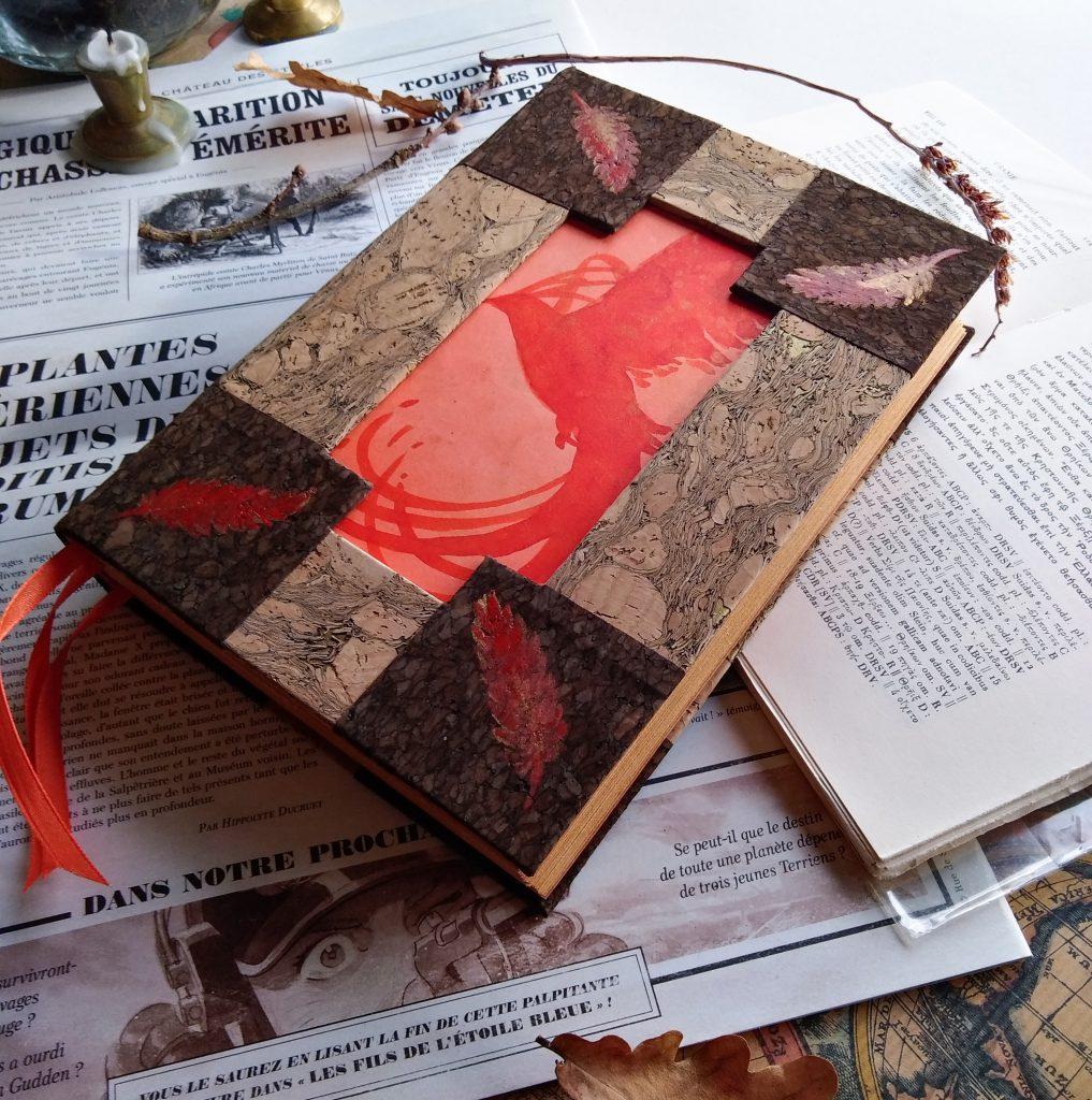 Photographie du grimoire du Phénix, fait avec deux nuances de liège, et une peinture de phénix encadré de plumes peintes à la main