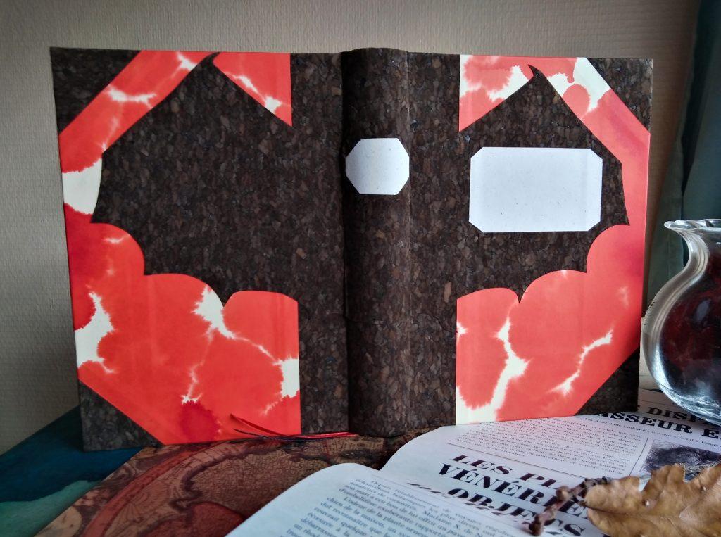 Photographie du grimoire du vampire, où l'on voit une chauve-souris déployée sur l'ensemble de la couverture, sur fond de papier évoquant des tâches de sang