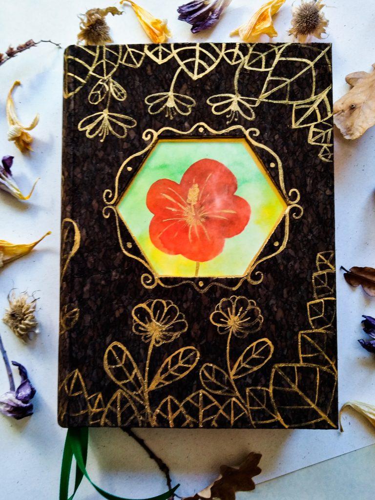 Photographie d'un grimoire en liège, décoré de fleurs dorées peintes à la main, avec une illustration centrale de fleurs rouges peinte à l'encre