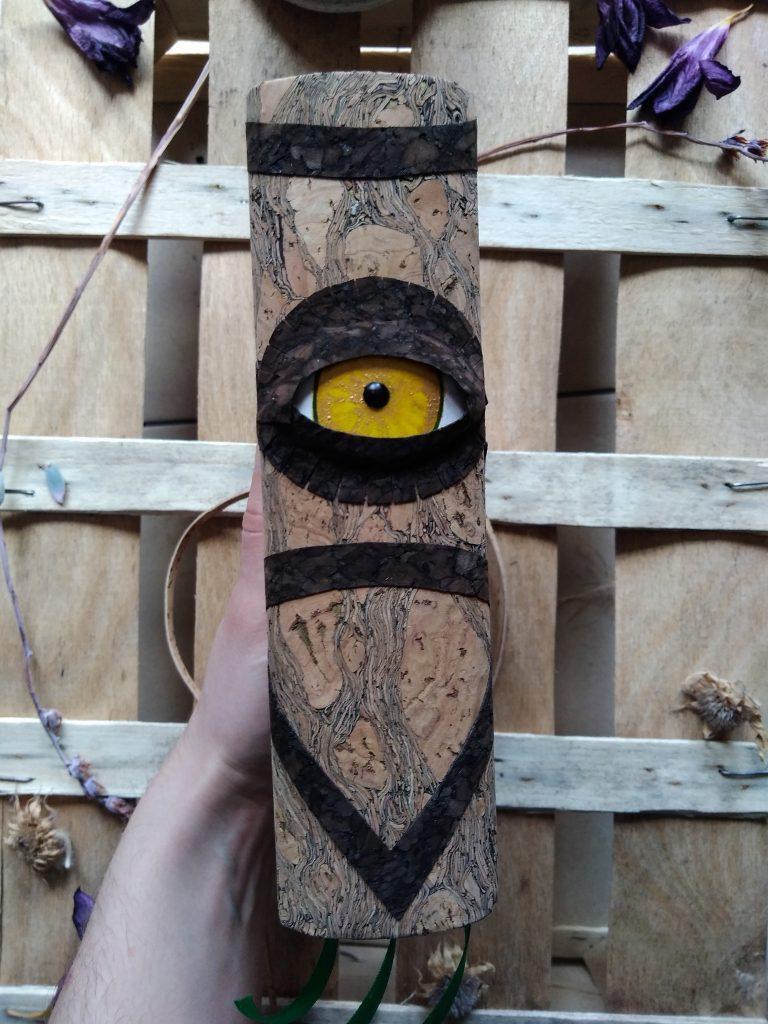 Photo d'un grimoire dont le dos est orné d'un oeil en trois dimension