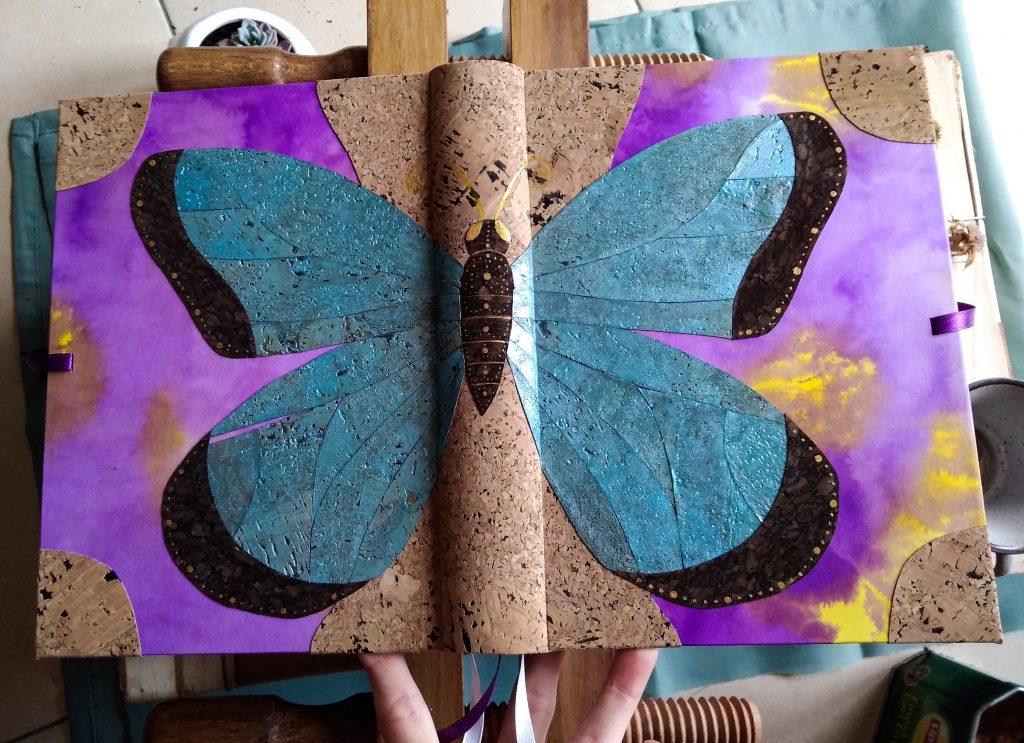 Photo du grimoire papillon, où l'on voit un papillon aux ailes bleues qui recouvre la couverture d'un livre en liège, avec un papier de couverture violet et jaune